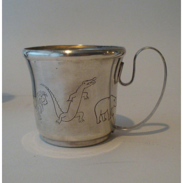 Charming silverplate baby's table set including a deep well plate, and cup with sipping lid. Both encircled with an...