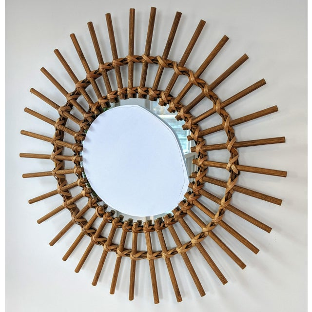 This wood and rattan mirror is handmade and features hand-wrapped wooden spokes in a sunburst pattern. The mirror is one...