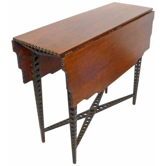 A wonderful and extremely unusual early 20th century drop-leaf table. Multi-directionally perforated, elegantly tapered...
