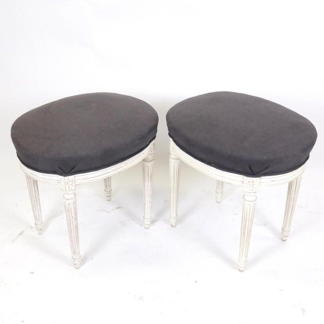 Elegant pair of Louis XVI style benches or ottomans, both oval shaped with reupholstered charcoal textile on painted...