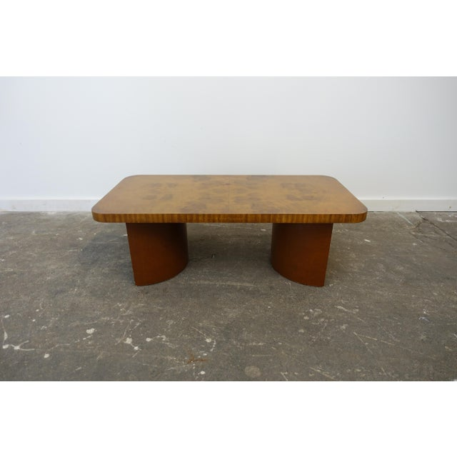 This coffee table has a burled wood top and studded leather wrapped base. This is an early modern design. There are some...