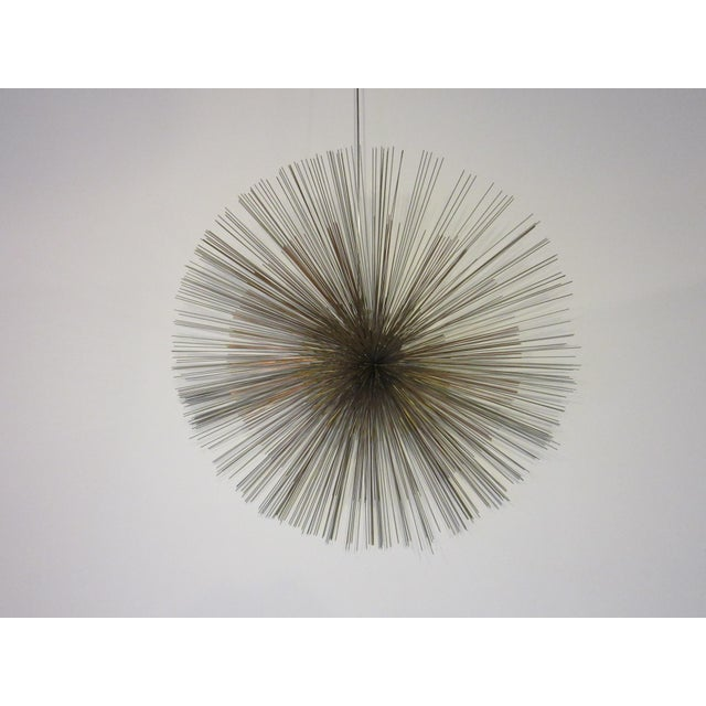 A large wire wall sculpture with multiple metal construction the center pom is brass the next one copper and the largest...