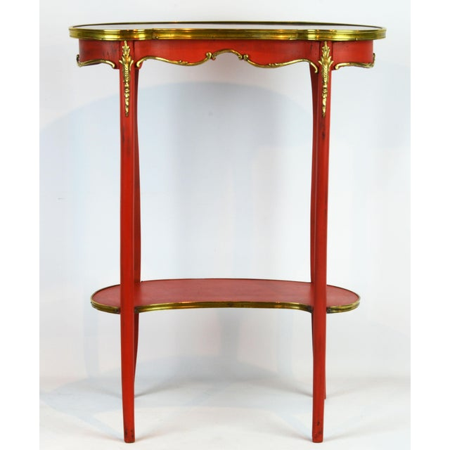 This charming late 19th century red painted table features a kidney shaped and bronze edged marble top above a scalloped...
