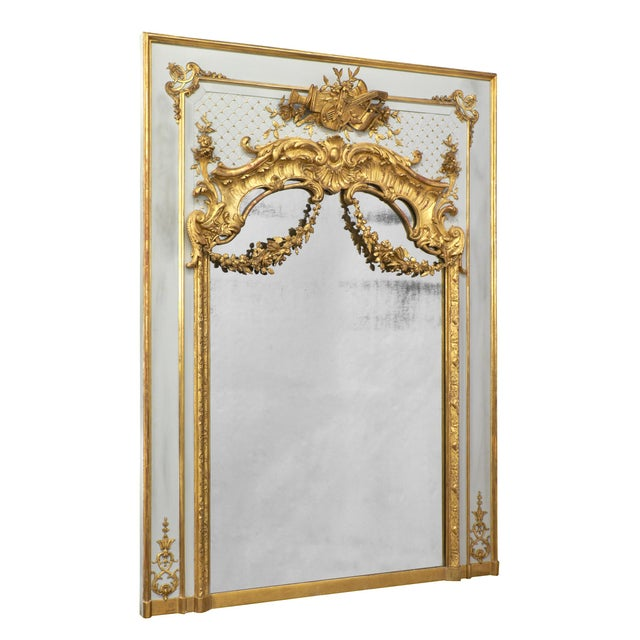 Magnificent antique French Louis XVI style trumeau resplendent with hand-carved, gold leafed décor surrounding the...