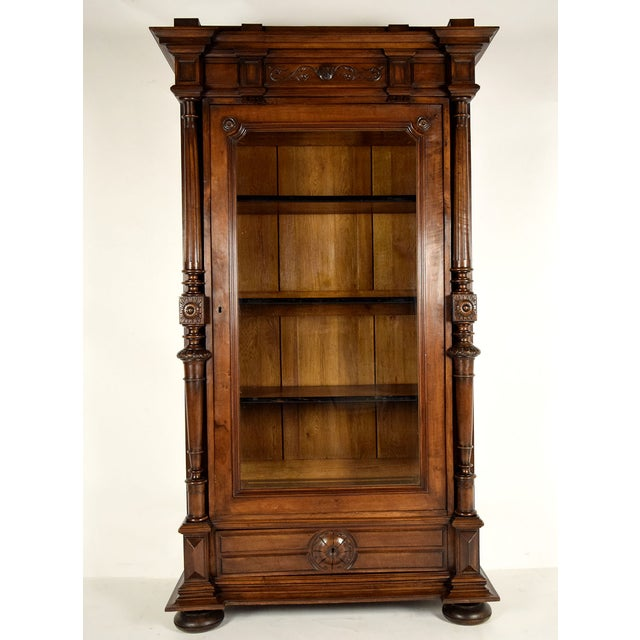 Here is an antique French single door bookcase from the 1860s. Made of solid walnut wood with an original rich dark walnut...