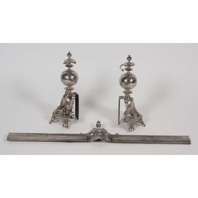 Chrome-plated chenet with adjustable frame and beautiful scroll work.