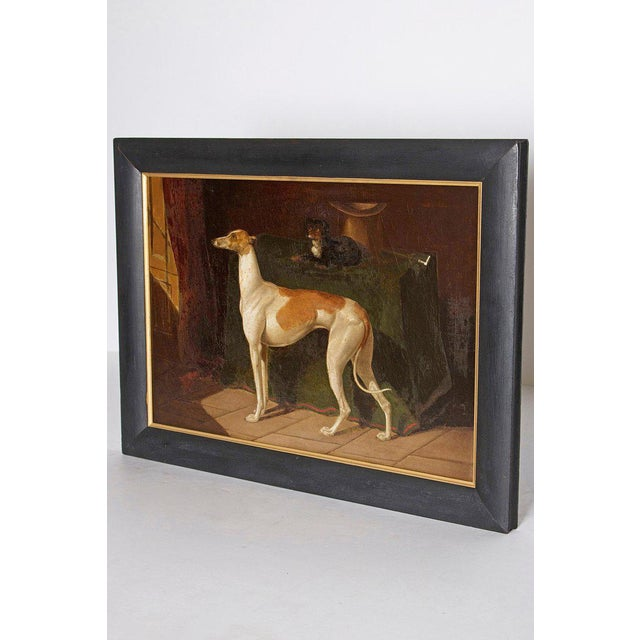 A realistically portrayed oil on canvas of a Whippet standing in an interior. The table top next to the Whippet has a...