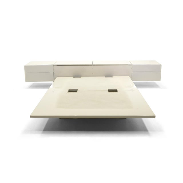 Queen-size platform bed by celebrated Montreal firm, Rougier, features a head board with lift up storage, flanked by...