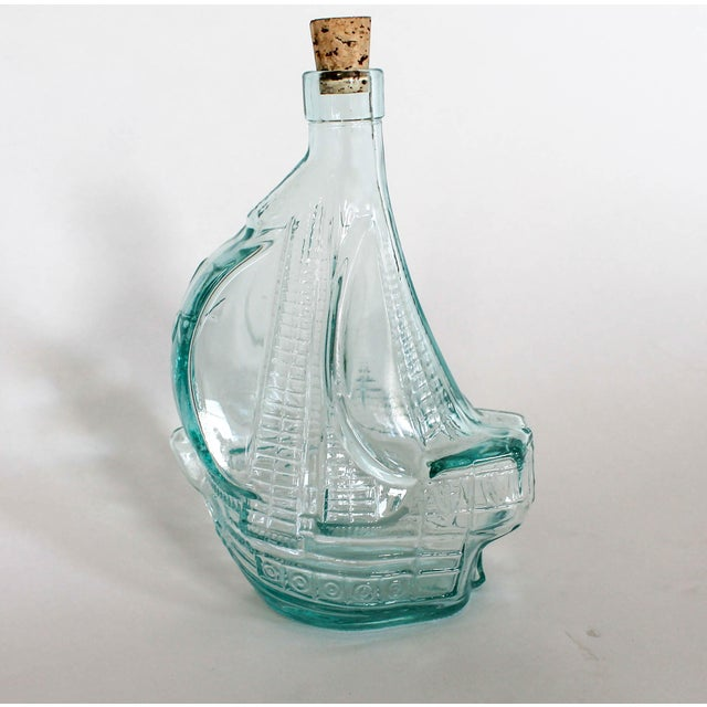 """Vintage glass bottle in the form of a ship with a cork. Marked """"Mod Dep 750 ml""""."""