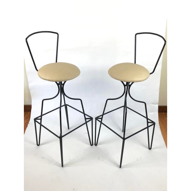 A modernist pair of Mid-Century wrought iron bar stools with a sculptural body, simple open frame backs, raised square...