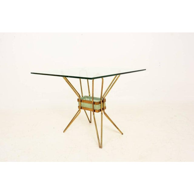 For your consideration a vintage Italian side table in brass and glass top. The sculptural legs are attached to a metal...