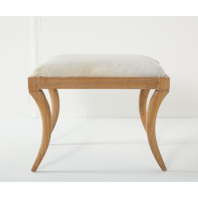 Cerused oak saber-leg ottoman with white pony hide seat, in the style of Jean-Michel Frank.
