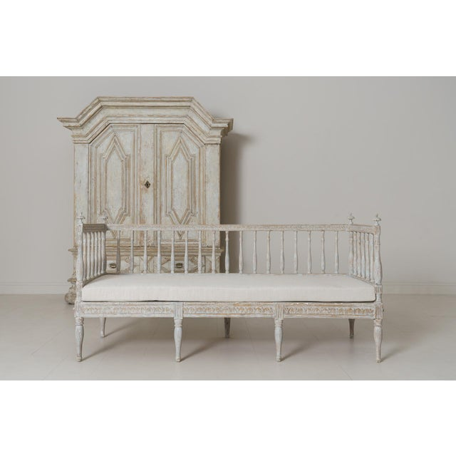 A Swedish Gustavian period sofa bench from the 19th century with a soft blue and aged white painted patina, newly...