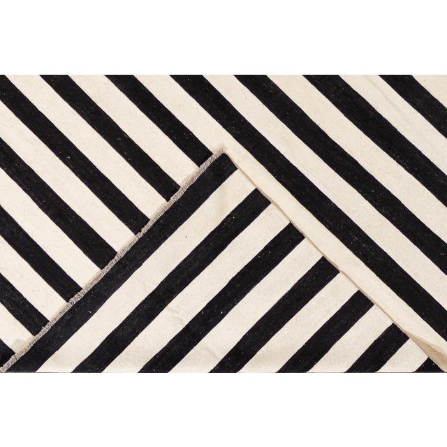 """A handwoven contemporary black and white striped Kilim rug. This handwoven flat-weave wool rug measures 9'1"""" x 11'9""""."""