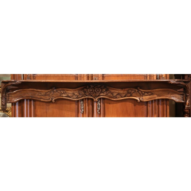 This elegant, antique, fruit wood shelf was crafted in Normandy, France circa 1840. The Louis XV wall hanging piece...