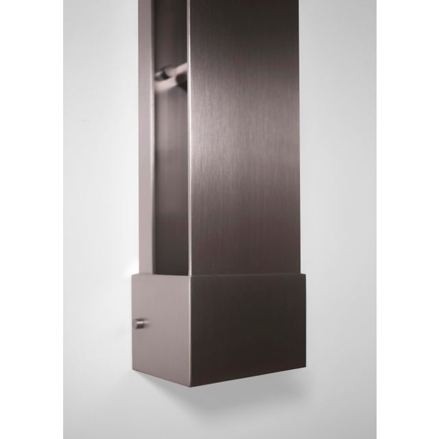 This contemporary light made of brushed nickel is part of the Orphan Work brand and can be used as a wall sconce, picture...