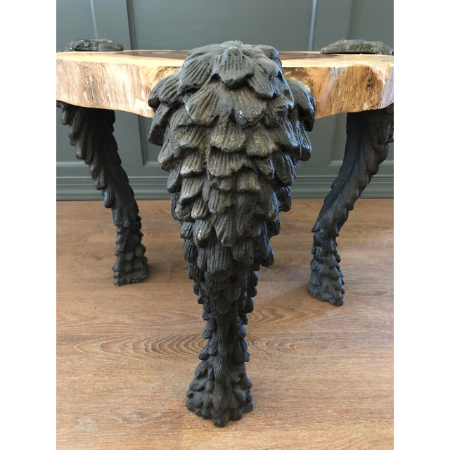 Three serpentine cast aluminum legs are finished in natural black and support the solid wood top. The waxed finish on the...