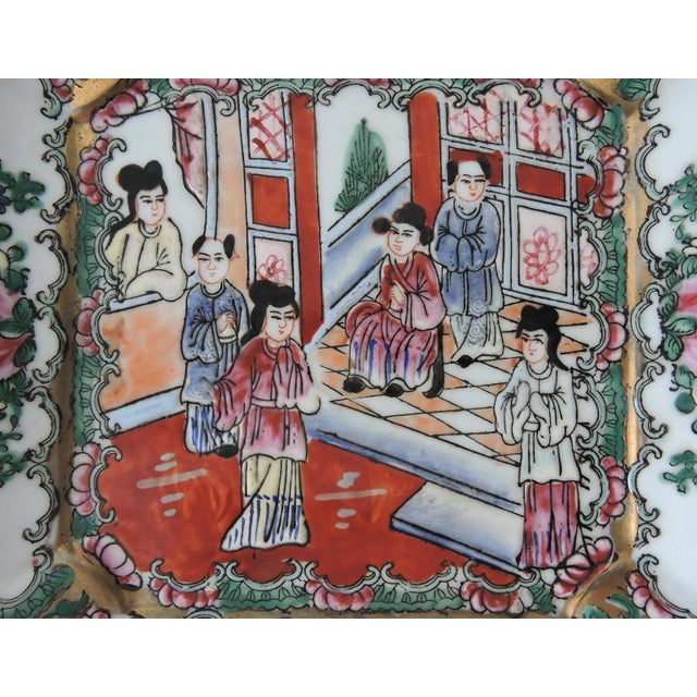 Square with raised edges, this traditional plate depicts inner Chinese court scenes. The piece features a gilt edge and...