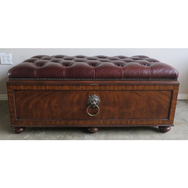 English Flamed Mahogany leather tufted trunk/blanket chest w/ storage. The chest stands on six bun feet and has brass lion...