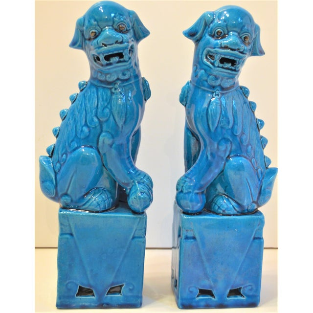 A pair of vintage turquoise mini Foo Dog statues. They are in a gorgeous ceramic with intricate designs around the base....