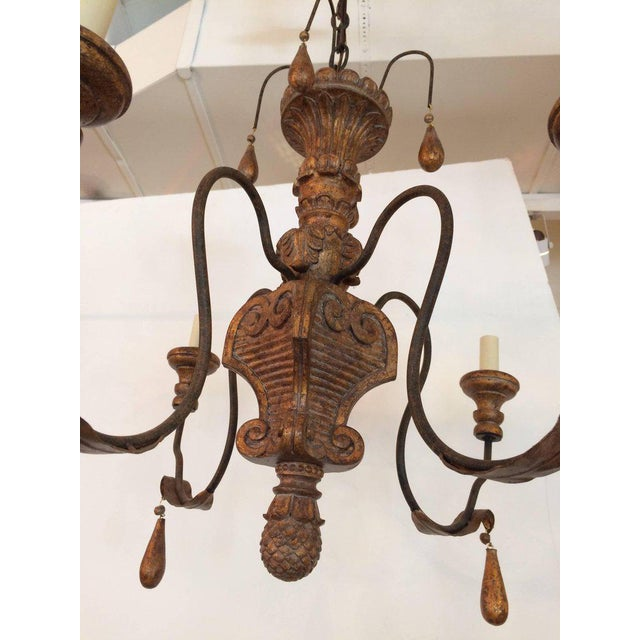 Old world style in a giltwood and iron fixture having four arms and tear drop embellishments.