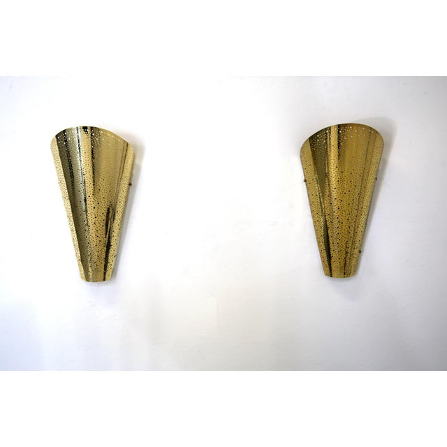 Golden wall sconce from modern wall. The wall lights are made of gold painted aluminum. The wall lights are conical in...