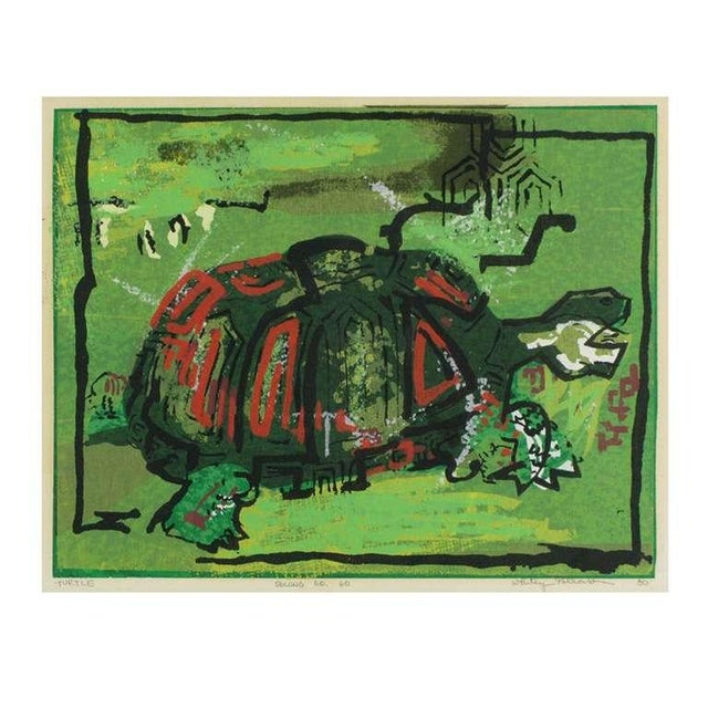 "Colorful block print of a red and green shelled turtle on a green background. Titled ""Turtle,"" numbered ""Second 60 60,..."