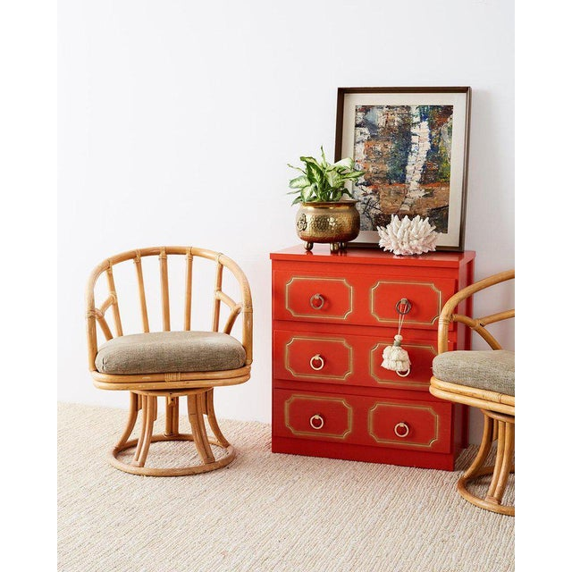 Colorful Dorothy Draper style commode or chest of drawers featuring a chic coral red lacquer with partial gilt accents....