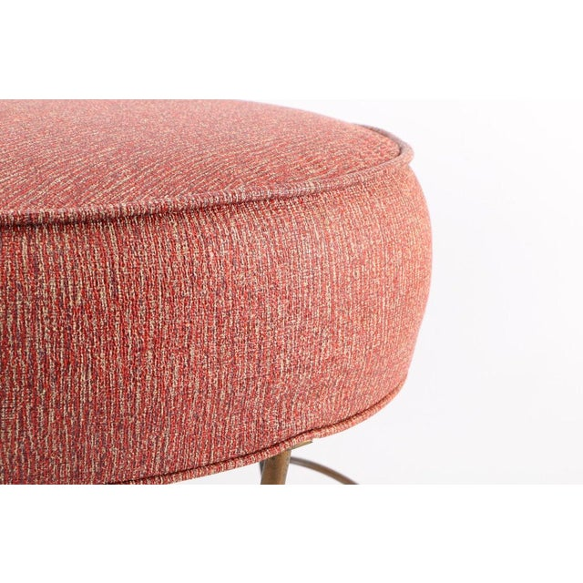 Form and function footrest by BT Crump. This piece features an upholstered circular top of light red coated fabric...