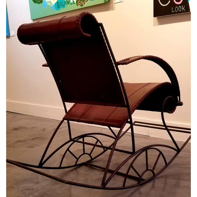 A leather rocking chair on a scrolled, solid iron frame. Scrolled headrest and seat, curved armrests, and leather...