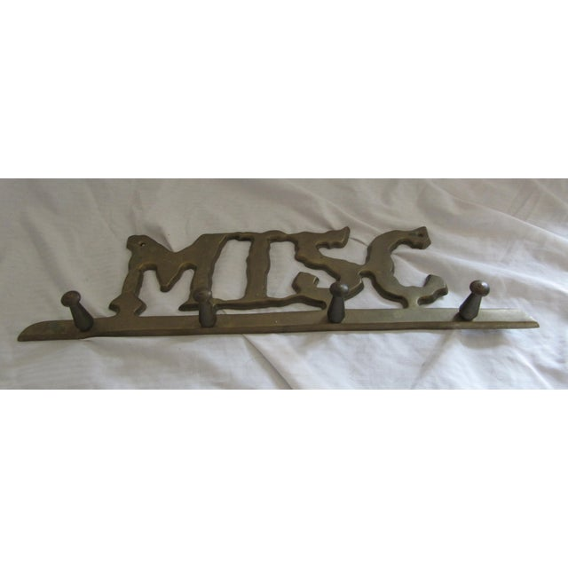 Vintage brass wall hook with Misc graphic.
