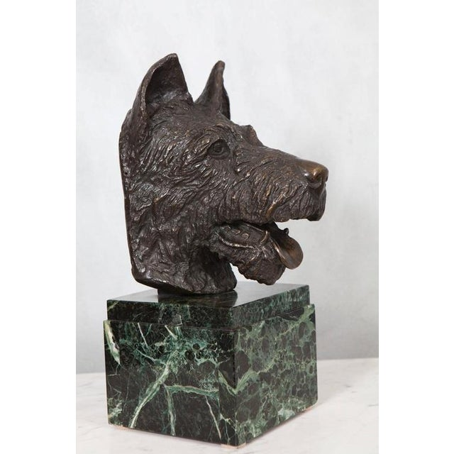 A delightful dog statue in bronze sits on a stepped marble block base. The detail of the casting and expression of the...