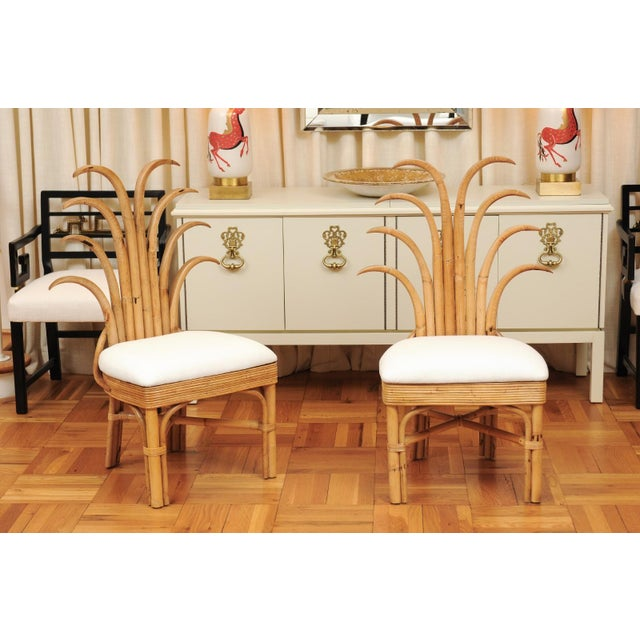 An absolutely majestic set of eight (8) custom made palm frond style dining chairs, circa 1950. Exceptionally conceived...