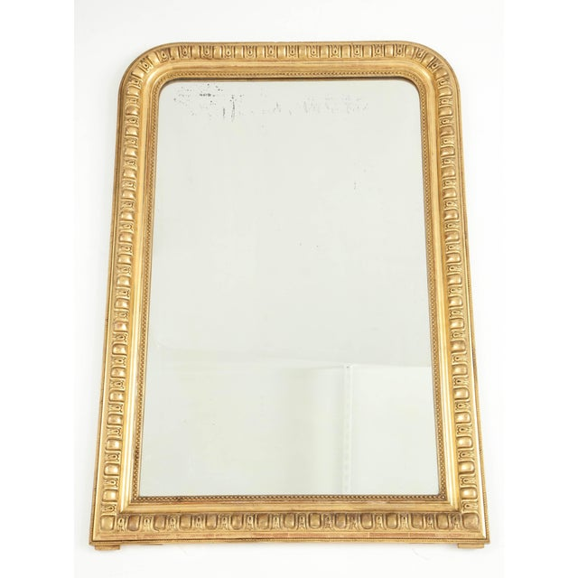This Louis Philippe giltwood mirror has unusual and carved detail in its giltwood frame and an inner beaded molding. The...