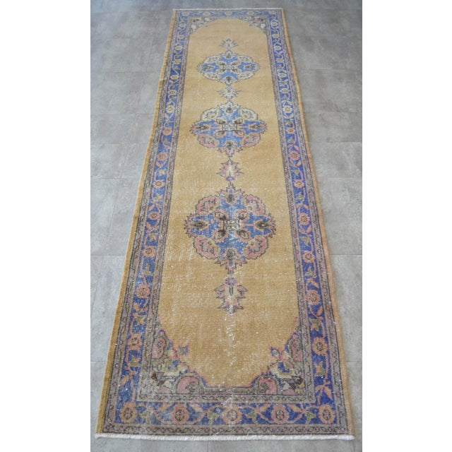 Vintage 1960s distressed Turkish Oushak rug runner. with ecru/sand field and shades of blue, rose and brown throughout....