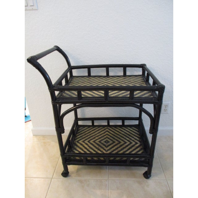 Stylish, well constructed rolling two-tier bar cart featuring a painted black bamboo frame with black and tan woven rattan...