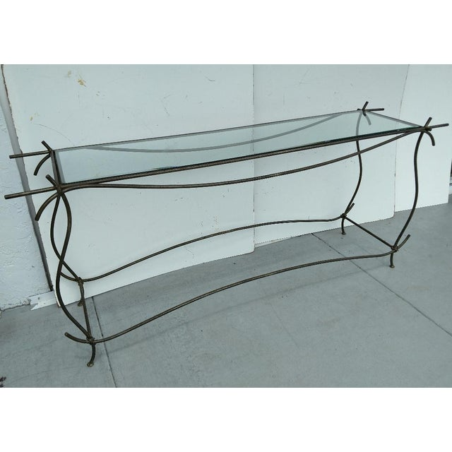 This wrought iron and glass console has beauty and grace in its sensual curved lines. The workmanship is excellent. The...