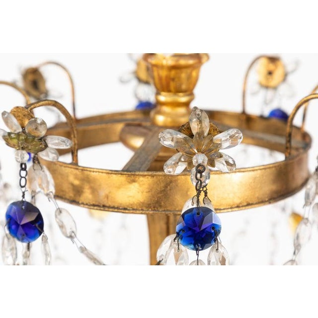 Pair of 18th century Italian giltwood and gilded iron chandeliers with sapphire and ruby colored crystals. All hand...