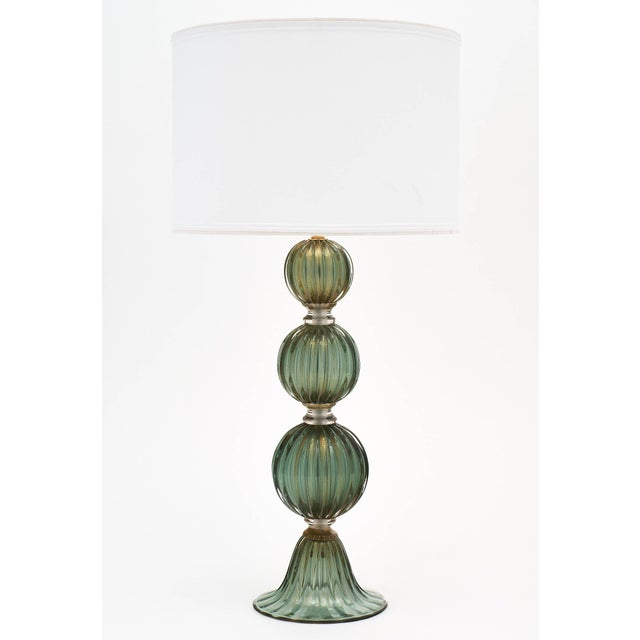 Green avventurina Murano glass lamps with four hand-blown segments of glass and a fluted base. The avventurina process...