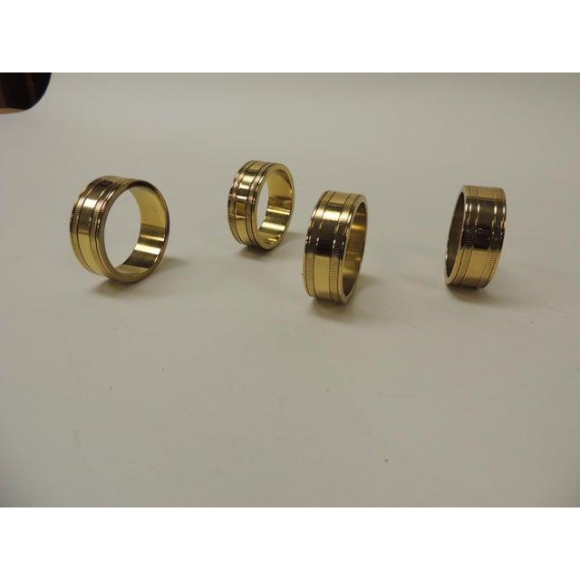 Set of (4) solid brass Ralph Lauren ribbon napkin holders. Size: 1 3/4 diameter x 1/2 wide.