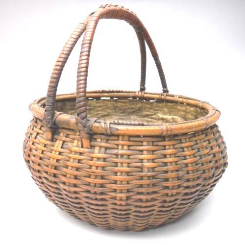 A simple Japanese woven bamboo ikebana basket made from natural 'susudake' or sooted bamboo in a casual 'sumikago' basket...