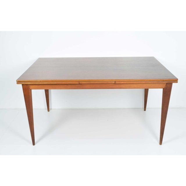 Teak dining table with recessed extension leaves.