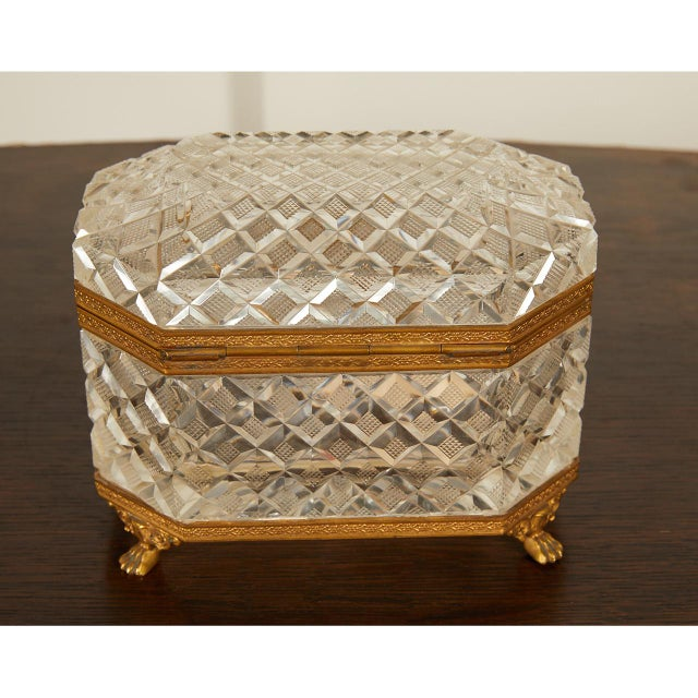 This lovely French bronze ormolu mounted footed casket has finely faceted and cut crystal with engraved ormolu bronze...