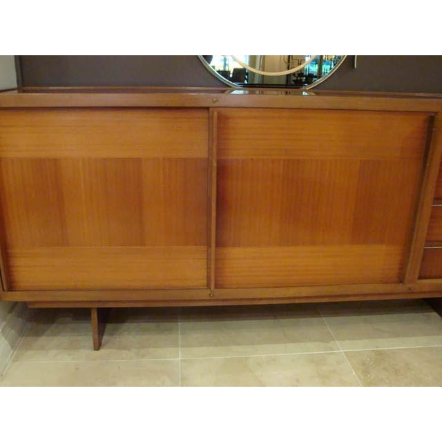 Mid-Century sideboard featuring a body in cross banded African Mahogany on a Mahogany base with two sliding doors which...