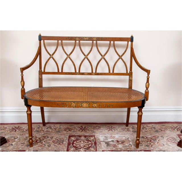 A stunning antique satinwood hand-painted, two-seat settee or bench with an elegantly pierced back, cane seat, gracefully...