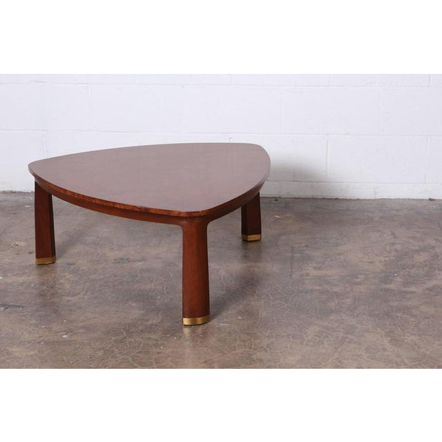 A triangle shaped table with Carpathian elm top and sculpted mahogany legs with brass feet. Designed by Edward Wormley for...