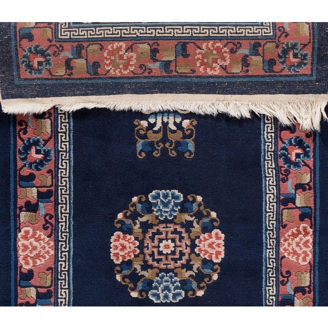 Apadana - Antique Chinese Peking carpet. This small piece has an intricate, light pink border, dark blue field, and floral...