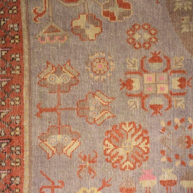 An early 20th century Central Asian Khotan carpet with three central medallions on a light indigo background amidst a...