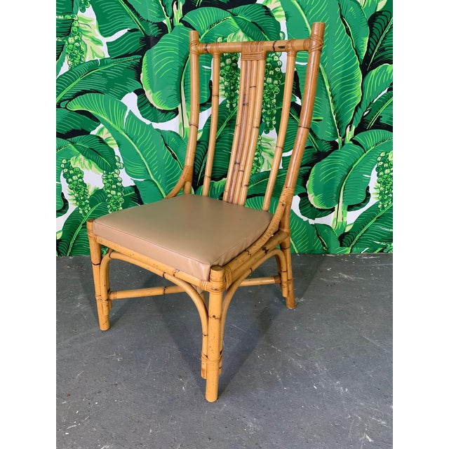 Set of 6 rattan dining chairs with sculptural bentwood form. Vinyl seat cushions that could easily be recovered. Very good...