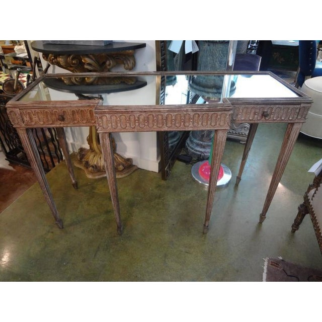 French Louis XVI style free standing console or sofa table. The piece features 3 drawers, fluted legs, and a mirrored top....